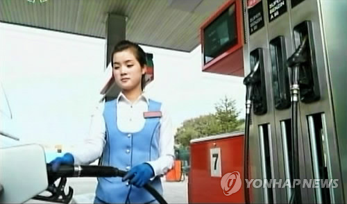 In this image, captured from the North's Korean Central TV on Jan. 16, 2014, shows an employee filling up a car with gas at a petrol station. (For Use Only in the Republic of Korea. No Redistribution) (Yonhap)