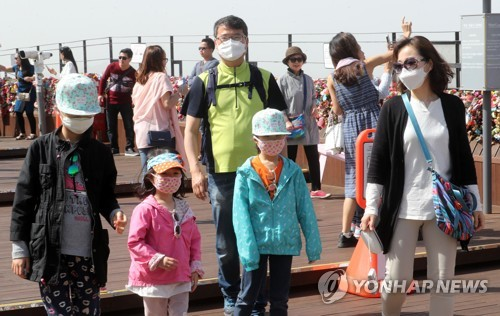 A family takes a stroll through Namsan Park in Seoul wearing protective masks with a fine dust advisory in place on May 6, 2017. (Yonhap)