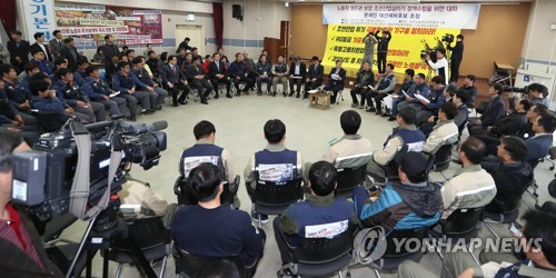 This photo taken on March 19, 2017, shows Moon Jae-in meeting with a group of shipyard workers in Changwon, South Gyeongsang Province, to listen to their difficulties. (Yonhap)