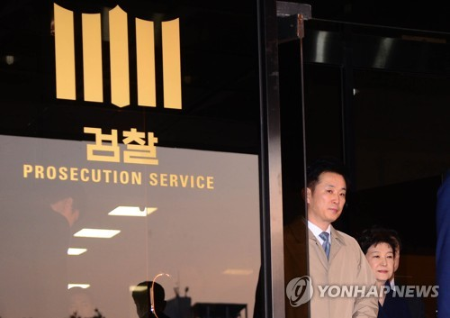 This photo taken on March 22, 2017, shows former President Park Geun-hye (R) leaving the Seoul Central District Prosecutors' Office in southern Seoul after overnight questioning on her corruption charges. (Yonhap)
