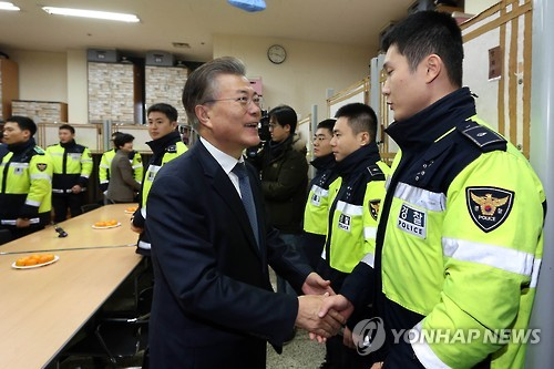 This file photo taken on Dec. 25, 2016, shows Moon Jae-in shaking hands with police officers at a police station in Seoul. (Yonhap)