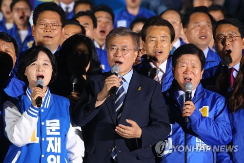 This photo, taken on May 8, 2017, shows Moon Jae-in (C), the then-presidential candidate of the liberal Democratic Party, and his party colleagues singing the national anthem during his election campaign in Seoul. (Yonhap)
