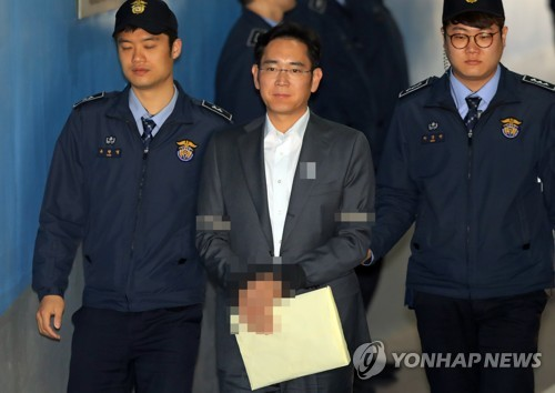 In this photo taken on April 19, 2017, Samsung Group's heir apparent Lee Jae-yong (C) moves to attend a court hearing in Seoul as part of an ongoing trial into a massive corruption scandal that led to the ouster of President Park Geun-hye in March. (Yonhap)