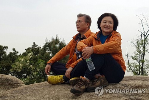Moon Jae-in (L) and his wife Kim Jung-sook are seated on a rock on a mountain near their home in northwestern Seoul on May 9, 2017. (Yonhap)