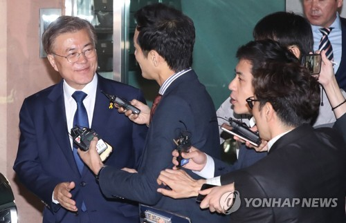 Moon Jae-in (L), the presidential candidate of the liberal Democratic Party, smiles to reporters while leaving his home in Seoul for the National Assembly where he was expected to be joined by party members and supporters for the outcome of the presidential election held May 9, 2017. An exit poll showed the liberal presidential candidate won the election with 41.4 percent of the votes. (Yonhap)