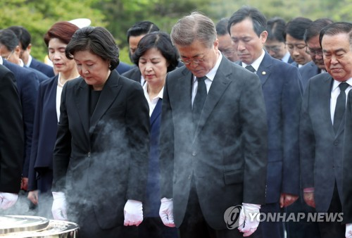 President Moon Jae-in (C) and first lady Kim Jung-sook (L) pay a silent tribute during their visit to the Seoul National Cemetery in southern Seoul on May 10, 2017. (Yonhap)