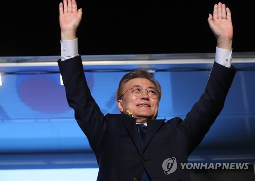 New South Korean President Moon Jae-in raises his arms in celebration of his victory in Seoul after the election on May 9, 2017. (Yonhap)