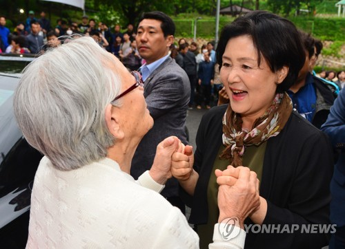 First lady Kim Jung-sook (R) says goodbye to a neighbor in front of the first couple's private residence in Hongeun-dong, Seoul, as she and her husband, Moon Jae-in, left the neighborhood on May 13, 2017, for the presidential residence. (Yonhap)