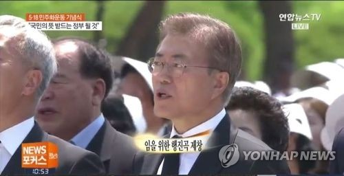 The captured image from Yonhap News TV shows President Moon Jae-in singing along to 'March for the Beloved' while attending a ceremony held May 18, 2017, in Gwangju to mark the 1980 democracy movement held in the city located 350 kilometers south of Seoul. The president made the controversial song an official part of the annual ceremony shortly after his inauguration on May 10, 2017. (Yonhap)