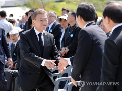 President Moon Jae-in (L) shakes hands with political leaders while attending an annual ceremony marking the 1980 democracy movement in Gwangju, 350 kilometers south of Seoul, on May 18, 2017. (Yonhap)