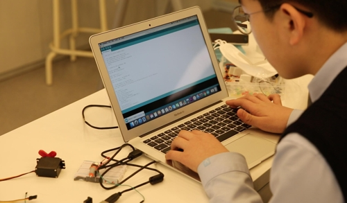 This photo provided by Code Academy on May 17, 2017, shows a student working on programming at the private institute in southern Seoul. (Yonhap)