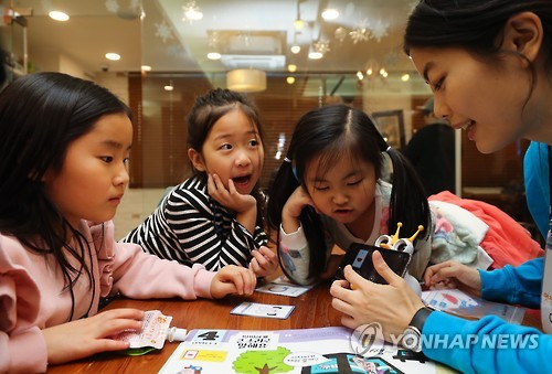 In this file photo taken on Dec. 14, 2016, a member of the non-profit foundation Like Lion teaches kids basic coding at a kids cafe in Seoul. (Yonhap)