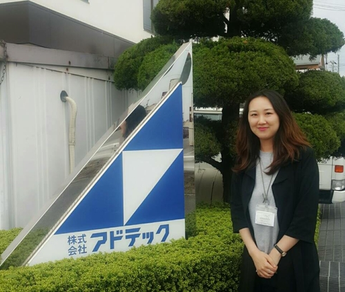 In this photo taken on May 17, 2017, and provided by Nam Yun-ha, a South Korean who work for Adtec Plasma Technology Co. in Osaka stands next to the company signboard. (Yonhap)