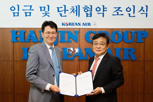 In this photo taken on May 17, 2017, and provided by Korean Air Lines, President and Chief Operating Officer Walter Cho (L) and the company's union leader Lee Jong-ho pose after signing a wage deal for 2016 at the airline's headquarters in western Seoul. (Yonhap)