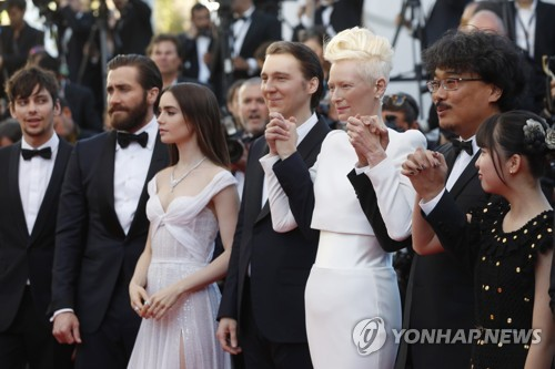 "In this AP photo, from right, actress Ahn Seo-hyun, director Bong Joon-ho, actors Tilda Swinton, Paul Dano, Lily Collins, Jake Gyllenhaal and Devon Bostick pose for photographers after their arrival at the screening of the film ""Okja"" at the 70th Cannes Film Festival in Cannes, southern France, on May 19, 2017. (Yonhap)"