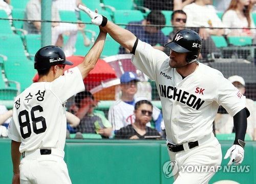 In this file photo taken on May 28, 2017, Jamie Romak of the SK Wyverns celebrates his home run with his third base coach Jung Soo-sung against the LG Twins during their Korea Baseball Organization regular season game at SK Happy Dream Park in Incheon. (Yonhap)