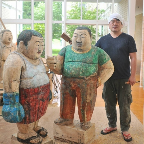 This undated photo, taken from Kim Won-geun's Facebook page on June 8, 2017, shows the sculptor standing next to his sculptures. (Yonhap)
