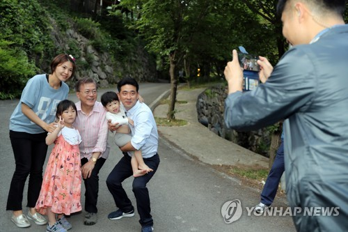 President Moon Jae-in (3rd from L) bends his knees to take a photo with a family at his personal residence in Yangsan, South Gyeongsang Province, on May 21, 2017. (Yonhap)