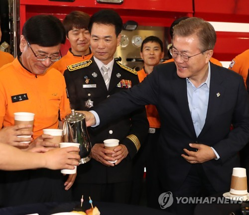 President Moon Jae-in pours coffee for firefighters during his visit to Yongsang Fire Station in central Seoul on June 7, 2017. (Yonhap)