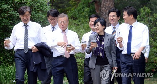 President Moon Jae-in (3rd from L) and his senior secretaries walk around Cheong Wa Dae, with coffees in their hands, on May 11, 2017. (Courtesy of Cheong Wa Dae)