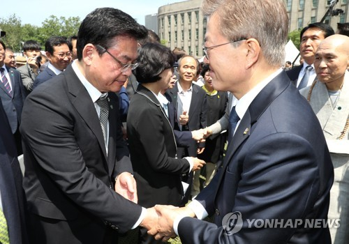 President Moon Jae-in shakes hands with Rep. Chung Woo-taik floor leader and acting chief of the main opposition Liberty Korea Party at a ceremony held in downtown Seoul