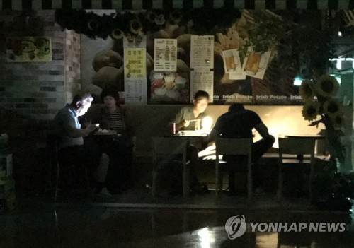 In this photo provided by a reader, diners at a restaurant eat in the dark after a power failure at Techno Mart in southwestern Seoul on June 11, 2017. (Yonhap)