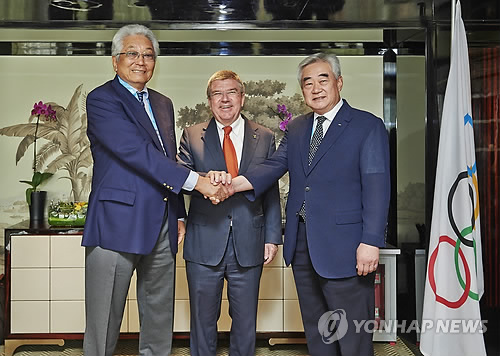 """In this file photo provided by the World Taekwondo Federation (WTF) on Aug. 25, 2014, Chang Ung, then president of the International Taekwondo Federation (L) shakes hands with WTF President Choue Chung-won (R), with International Olympic Committee President Thomas Bach in the middle, in Nanjing, China, on the sidelines of the Youth Olympic Games in Nanjing, China. Chang and Chung signed """"Protocol of Accord,"""" an agreement detailing efforts to promote cooperation between the two organizations. (Yonhap)"""