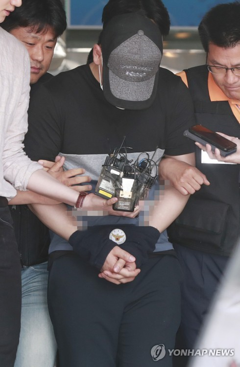 The suspect in a recent bomb blast at Yonsei University is surrounded by reporters as the police take him to a court on June 15, 2017. (Yonhap)