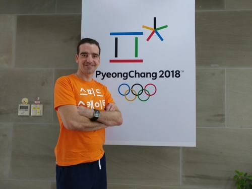 "Bob de Jong, an assistant coach for the South Korean speed skating team from the Netherlands, poses next to the banner for the 2018 PyeongChang Winter Olympics at the National Training Center in Seoul on June 16, 2017. His t-shirt says ""speed skating"" in Korean. (Yonhap)"