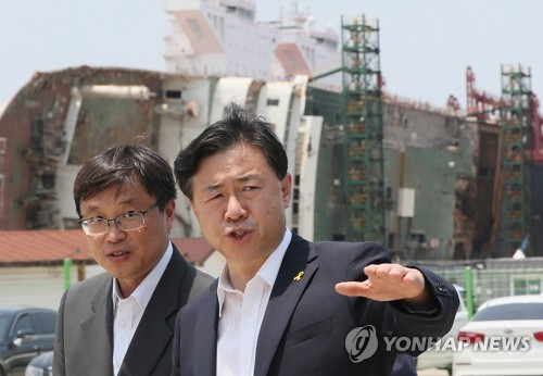 Oceans and Fisheries Minister Kim Young-choon (R) talks to an official during a visit to the dock where the salvaged Sewol ferry is placed in Mokpo, southwest of Seoul, on June 17, 2017 (Yonhap)