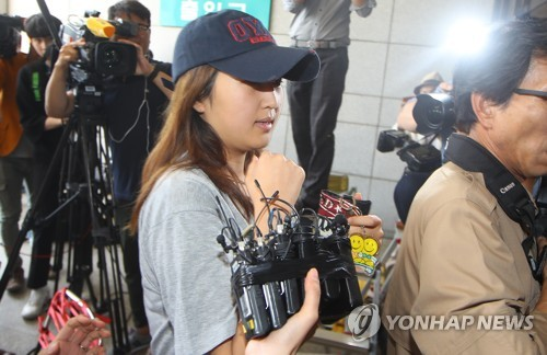 Chung Yoo-ra, the daughter of former President Park Geun-hye's close associate, Choi Soon-sil, is brought to the prosecution in Seoul on June 13, 2017, for questioning on various allegations ranging from illegal university admissions to foreign exchange law breaches. (Yonhap)