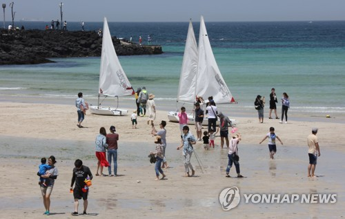 "Tourists walk on a beach on the southern resort island of Jeju on May 7, 2017, the final day of a ""golden holiday week"" in South Korea. (Yonhap)"
