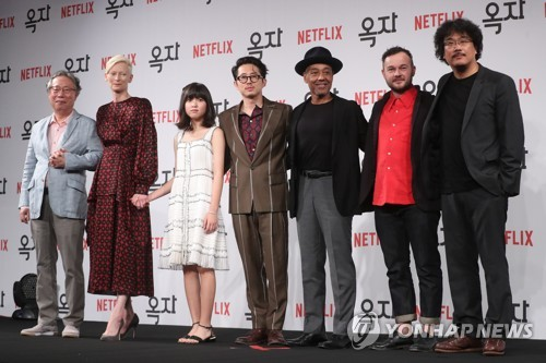 "The cast of ""Okja"" -- Byun Hee-bong, Tilda Swinton, An Seo-hyun, Steven Yeun, Giancarlo Esposito and Daniel Henshall (from L to R) -- and director Bong Joon-ho (R) pose for the camera during a press conference for the film in Seoul on June 14, 2017. (Yonhap)"