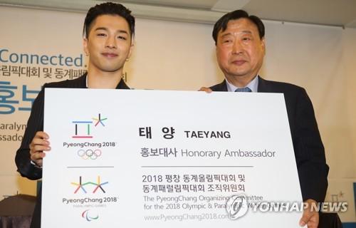 BIGBANG's Taeyang holds up a card showing him as an honorary ambassador for the 2018 Pyeong Chang Winter Olympics alongside Lee Hee-beom head of PyeongChang's organizing committee at a ceremony in Seoul