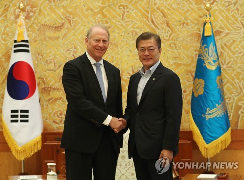 South Korean President Moon Jae-in shakes hands with Richard Haass president of U.S. think tank Council on Foreign Relations in a meeting at the presidential office Cheong Wa Dae