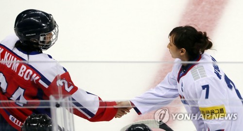 In this file photo, taken on April 7, 2017, South Korean women's hockey captain Lee Kyou-sun (R) shakes hands with her North Korean counterpart Kim Kum-bok before their game at the International Ice Hockey Federation Women's World Championship Division II Group A tournament at Gangneung Ice Arena in Gangneung, Gangwon Province. (Yonhap)