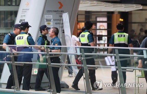 Police officers are seen busy conducting a sweeping search at the Shinhan FAN Square hall on June 26, 2017, in western Seoul after an anonymous man threatened to bomb a media showcase event by K-pop girl group Apink. (Yonhap)
