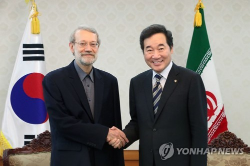 This photo, taken on June 28, 2017, shows South Korea's Prime Minister Lee Nak-yon (R) shaking hands with Iranian parliamentary speaker Ali Larijani before their talks at Lee's office in Seoul. (Yonhap)