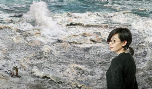 "The photo provided by artist Won Seoung-won shows her posing  in front of  ""The Sea of Journalists"" on display at Arario Gallery in Seoul. (Yonhap)"