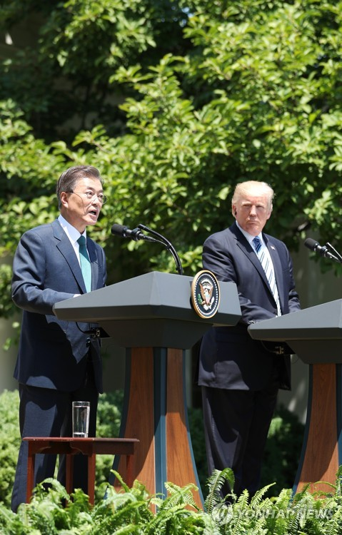 South Korean President Moon Jae-in (L) and U.S. President Donald Trump hold a joint press conference following their bilateral summit at the White House on June 30, 2017. (Yonhap)