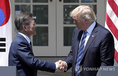 South Korea President Moon Jae-in (L) and U.S. President Donald Trump shake hands after a joint press conference that followed their first summit at the White House on June 30, 2017. (Yonhap)