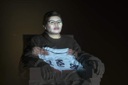 The image provided by the National Museum of Modern and Contemporary Art (MMCA) on July 4, 2017, shows the image of the mother of Oh Joon-young, one of the victims in the 2014 Sewol ferry sinking, projected on to the statue of Kim Koo. (Yonhap)