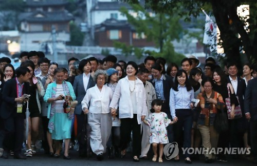 This photo, taken on June 26, 2017, shows first lady Kim Jung-sook (C) walking with citizens on a road near the presidential compound Cheong Wa Dae in Seoul. (Yonhap)
