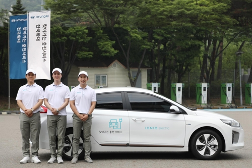 In this photo taken on July 17, 2017, Hyundai Motor employees stand before the carmaker's charging service vehicle in Seoul. (Courtesy of Hyundai Motor) (Yonhap)