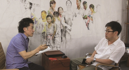 """In this photo taken by Jean Lee and provided by BG Muhn shows the professor interviewing North Korean artist Kim In-sok at the Mansudae Art Museum in Bejing, China on May 20, 2016. In the background shows Kim's work in progress """"Rain Shower at the Bus Stop."""" (Yonhap)"""