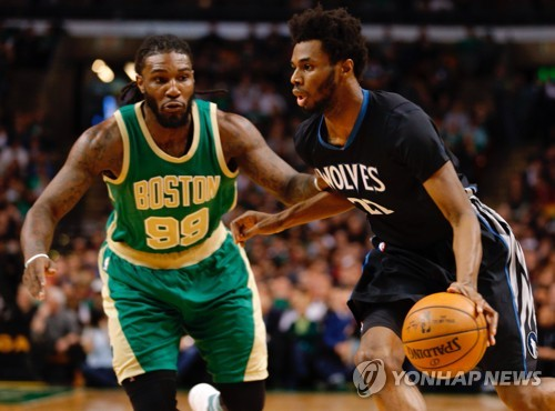In this EPA file photo taken on March 15, 2017, Andrew Wiggins of the Minnesota Timberwolves (R) drives past Jae Crowder of the Boston Celtics during their National Basketball Association game at TD Garden in Boston. (Yonhap)