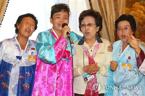 """This file photo, taken on Oct. 25, 2015, shows separated South and North Korean families singing the song """"Our wish is unification"""" together at family reunions. (Yonhap)"""