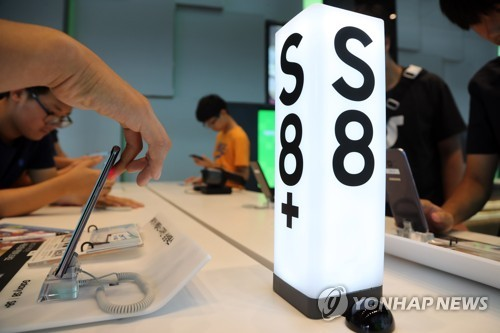 Visitors test Samsung Electronics Co.'s Galaxy S8 smartphones at a company shop in Seoul