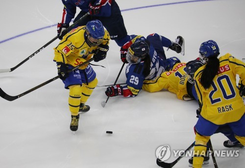South Korean women's hockey forward Grace Lee (C) falls to the ice in a battle against Sweden during the teams' friendly game at Gangneung Hockey Centre in Gangneung, Gangwon Province, on July 28, 2017. (Yonhap)