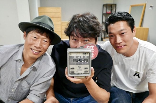 """In this photo released by Showbox, three members of the main cast of """"A Taxi Driver"""" -- Yoo Hae-jin, Song Kang-ho and Choi Gui-hwa (L to R) -- pose for the camera in celebration of the film attracting over 5 million viewers. (Yonhap)"""